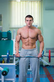 Man makes exercise. Man at the gym. Man makes exercises with barbell. Sport, power, dumbbells, tension, exercise - the concept of a healthy lifestyle. Article Royalty Free Stock Photos