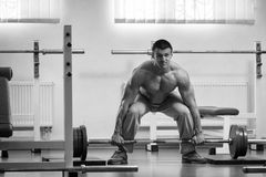 Man makes exercise. Man at the gym. Man makes exercises with barbell. Sport, power, dumbbells, tension, exercise - the concept of a healthy lifestyle. Article Stock Images