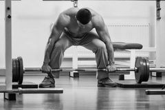 Man makes exercise. Man at the gym. Man makes exercises with barbell. Sport, power, dumbbells, tension, exercise - the concept of a healthy lifestyle. Article Stock Image
