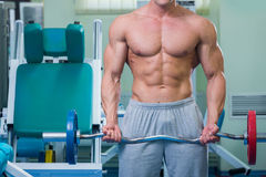 Man makes exercise. Man at the gym. Man makes exercises with barbell. Sport, power, dumbbells, tension, exercise - the concept of a healthy lifestyle. Article Royalty Free Stock Image