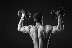 Man makes exercises dumbbells. Sport, power, dumbbells, tension, exercise. Article about fitness and sports.Gym and fitness concept - bodybuilder and dumbbell Royalty Free Stock Image