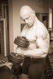 Man makes exercises dumbbells Stock Photos