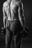 Man makes exercises dumbbells Stock Images