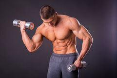 Man makes exercises dumbbells stock image