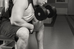 Man makes exercises dumbbells. Sport, power, dumbbells, tension, exercise. Article about fitness and sports.Gym and fitness concept - bodybuilder and dumbbell stock photos