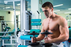 Man makes exercises dumbbells. Sport, power, dumbbells, tension, exercise. Article about fitness and sports.Gym and fitness concept - bodybuilder and dumbbell stock photo