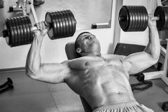 Man makes exercises dumbbells Stock Photos