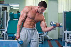 Man makes exercises. Man at the gym. Man makes exercises. Sport, power, dumbbells, tension, exercise - the concept of a healthy lifestyle. Article about fitness Royalty Free Stock Photo