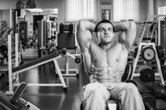 Man makes exercises. Man in the gym. Working out with weights.Man makes exercises. Sport, power, dumbbells, tension, exercise - the concept of a healthy Royalty Free Stock Images