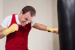 Man makes exercises with punching bag Royalty Free Stock Photos