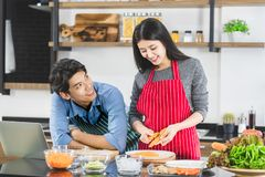 Man makes eye contact with woman in kitchen. Close up shot of Asian couple in apron, men make eye contact with women that grates the carrot into strips, in stock photography