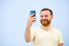A man makes faces in a funny and humorous phone makes serious faces, an advertising company. Man makes faces in a funny and humorous phone makes serious faces Stock Images