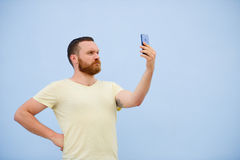 A man makes faces in a funny and humorous phone makes serious faces, an advertising company. Man makes faces in a funny and humorous phone makes serious faces Royalty Free Stock Photo
