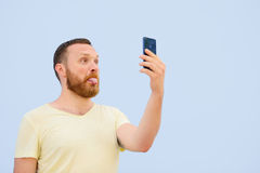 Man makes faces in a funny and humorous phone shows a language, an advertising company.  Royalty Free Stock Images