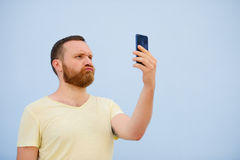 Man makes faces in a funny and humorous phone shows a language, an advertising company.  Royalty Free Stock Photo