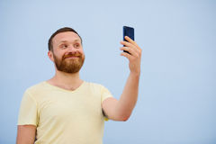 Man makes faces in a funny and humorous phone shows a language, an advertising company.  Stock Photography