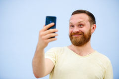Man makes faces in a funny and humorous phone shows a language, an advertising company.  Stock Photo