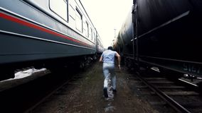 Man makes a fight with a shadow among two trains. A man makes a fight with a shadow among two trains and runs off with acceleration stock video footage