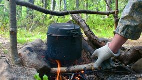 Man makes a fire for cooking in the forest, putting firewood on the fire