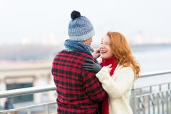Man makes funny ginger woman in red scurf. Guy cares about woman. Woman happy to meet man in city. Man makes funny red hair woman in red scurf. Guy carring Royalty Free Stock Photos