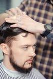 Man makes a haircut at barbershop Royalty Free Stock Photos