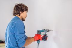 A man makes a hole in the wall with a drill stock photography