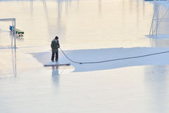 Man makes ice on a skating rink. Royalty Free Stock Photos