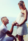 Man makes a marriage proposal at his pregnant wife Stock Image