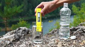 Man makes measurement of PH in glass of clean water on mountain area. Theme of health and ecology. Slowmotion. Man makes measurement of PH in glass of clean stock video