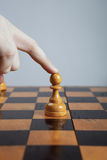 Man makes a move chess pawn Stock Photography
