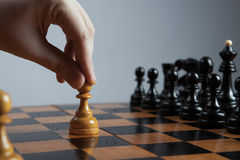 Man makes a move chess pawn Stock Photos