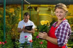 The man makes notes about the observation of the growth of the yellow flower in the pot, which is kept by the girl in the greenhou. The men makes notes about the stock photography