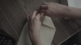 A man makes paper plane close up stock video footage