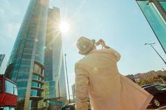Man makes photo shoot of skyscrapers in the big city. Travel and lifestyle concept. Stock Image