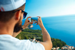 Man makes photos by a smartphone on the background of sea coast, Stock Photos