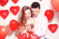 Man makes present to his lovely sweetheart girl. Lover`s valentine day. Valentine Couple. Boy gives to his girlfriend jewelry. royalty free stock images