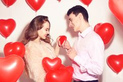 Man makes present to his lovely sweetheart girl. Lover`s valentine day. Valentine Couple. Man gives to his girlfriend sweets. At heart box. Background red stock image