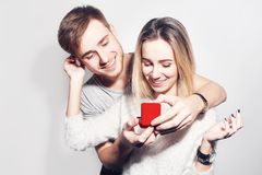 Man Makes Present To His Lovely Sweetheart Girl. Young Man Giving A Gift. Couple Offering To Each Other Gifts For Lover`s Stock Photography