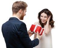 Man makes present to his sweetheart. Man makes present to his lovely sweetheart, isolated on white Stock Photos