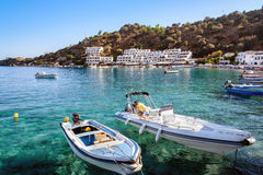 Man makes a repeir of motorboat in bay of Loutro town on Crete island Stock Photo