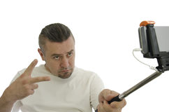 Man makes a selfie with  stick. Man makes a selfie with stick on white background Stock Photography