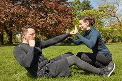 Man makes sit-ups with Personal fitness Trainer royalty free stock photos