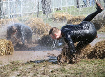 A man makes a spectacular overturn in the mud. STOCKHOLM - MAY 09, 2015: A man makes a spectacular overturn in the mud trying to avoid the hanging electrified Stock Images