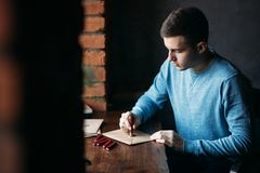 Man makes the stamp using sealing wax on the envelope stock photo