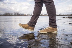 Man makes a step into the water. Man hipster makes a step into the water of the river royalty free stock photo