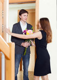 Man makes surprise to his young wife with bunch of flowers. At home door royalty free stock photography