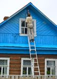 The man makes up a facade of the wooden house, standing on a ladder Stock Photos