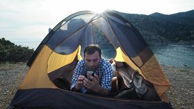 A man makes a video call to friends, relatives or boyfriend to show him the beautiful place where camp with the tent. Camp tent stands on the seashore stock video footage