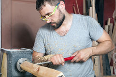 Man  makes a wooden product on a lathe Royalty Free Stock Photography