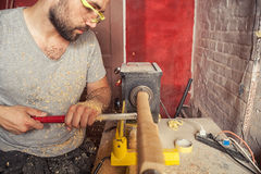 Man  makes a wooden product on a lathe Royalty Free Stock Photo